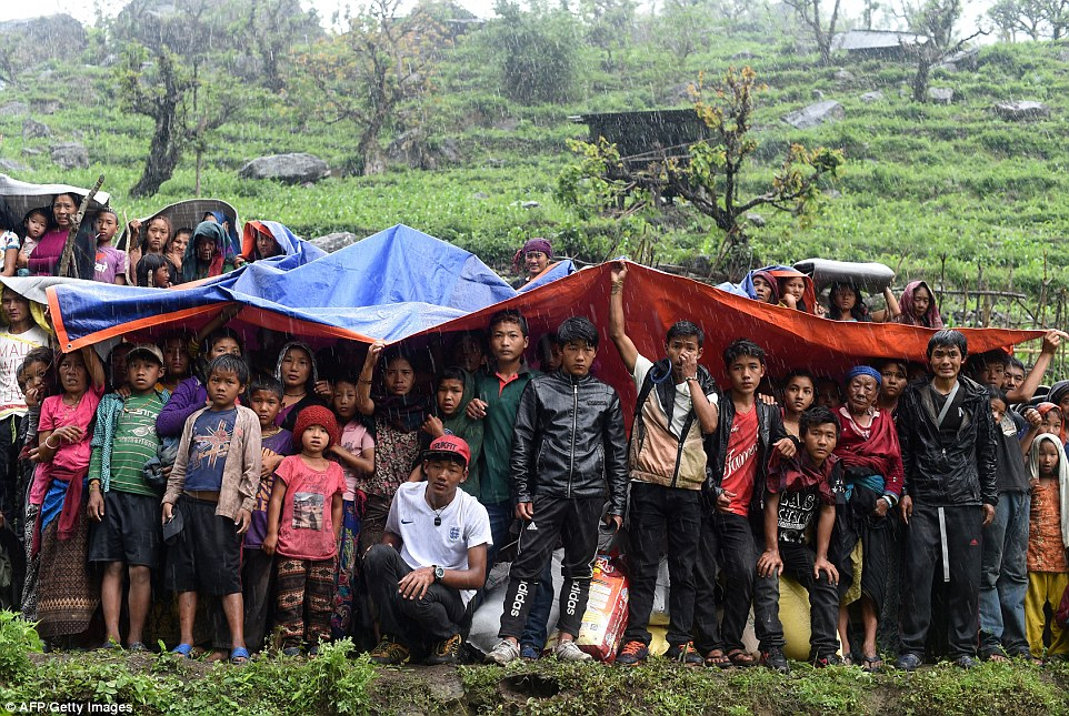28185B8300000578-3058707-Nepalese_villagers_shelter_from_rain_under_plastic_sheets_as_an_-a-11_1430218769489